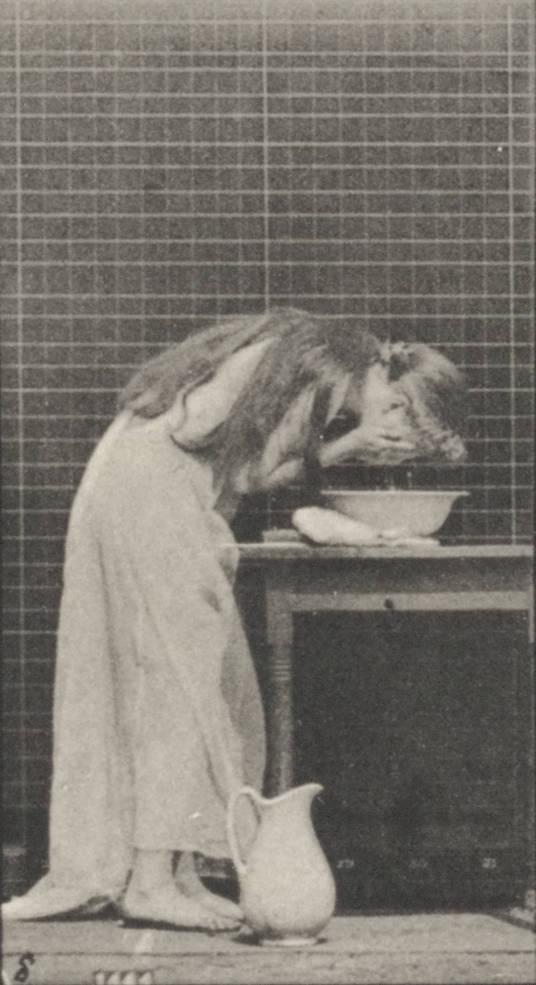 Woman_brushing_hair_and_washing_face_(rbm-QP301M8-1887-496a-8)