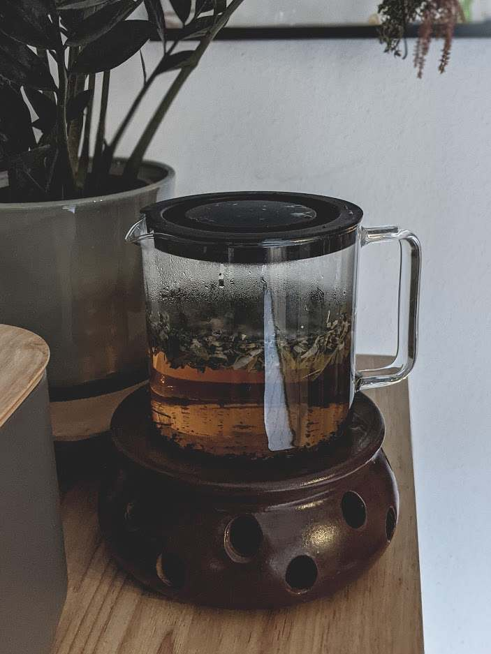Haar-Tee in Glaskanne auf einem braunen Stövchen
